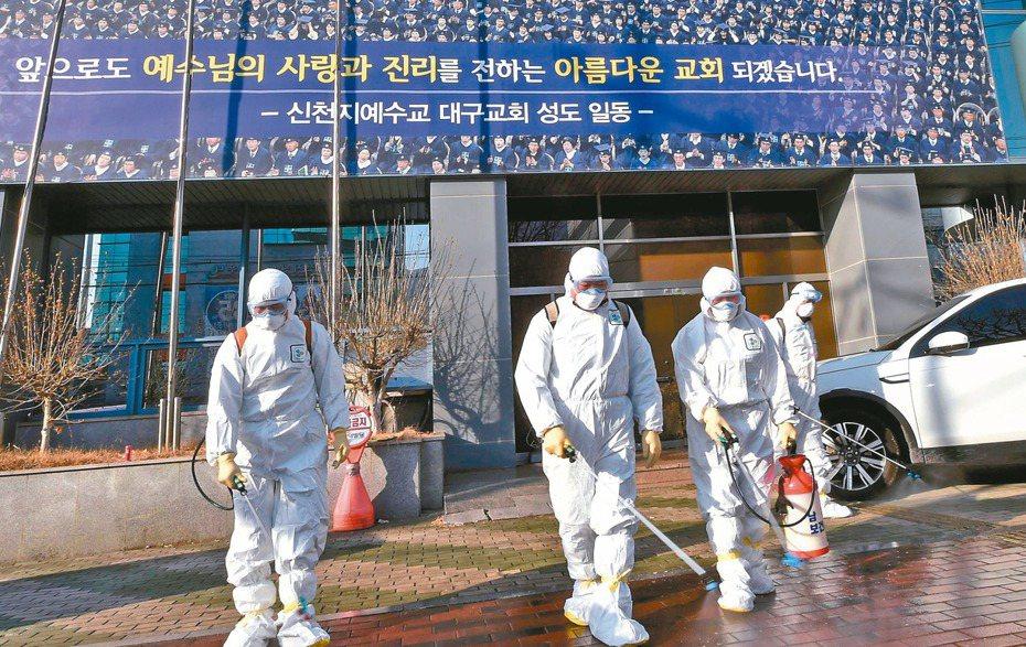 南韓新增52個新冠肺炎確診病例。圖為南韓衛生站人員在噴霧消毒。 (法新社)