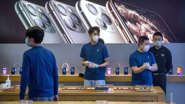 北京一家蘋果零售店員工戴上口罩,等顧客上門。蘋果警告本季營收受新冠肺炎疫情影響,...
