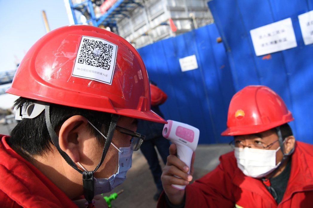 甘肅蘭州石化工程項目復工,施工人員先測量體溫後,再憑安全帽上的疫情防控准入證二維...