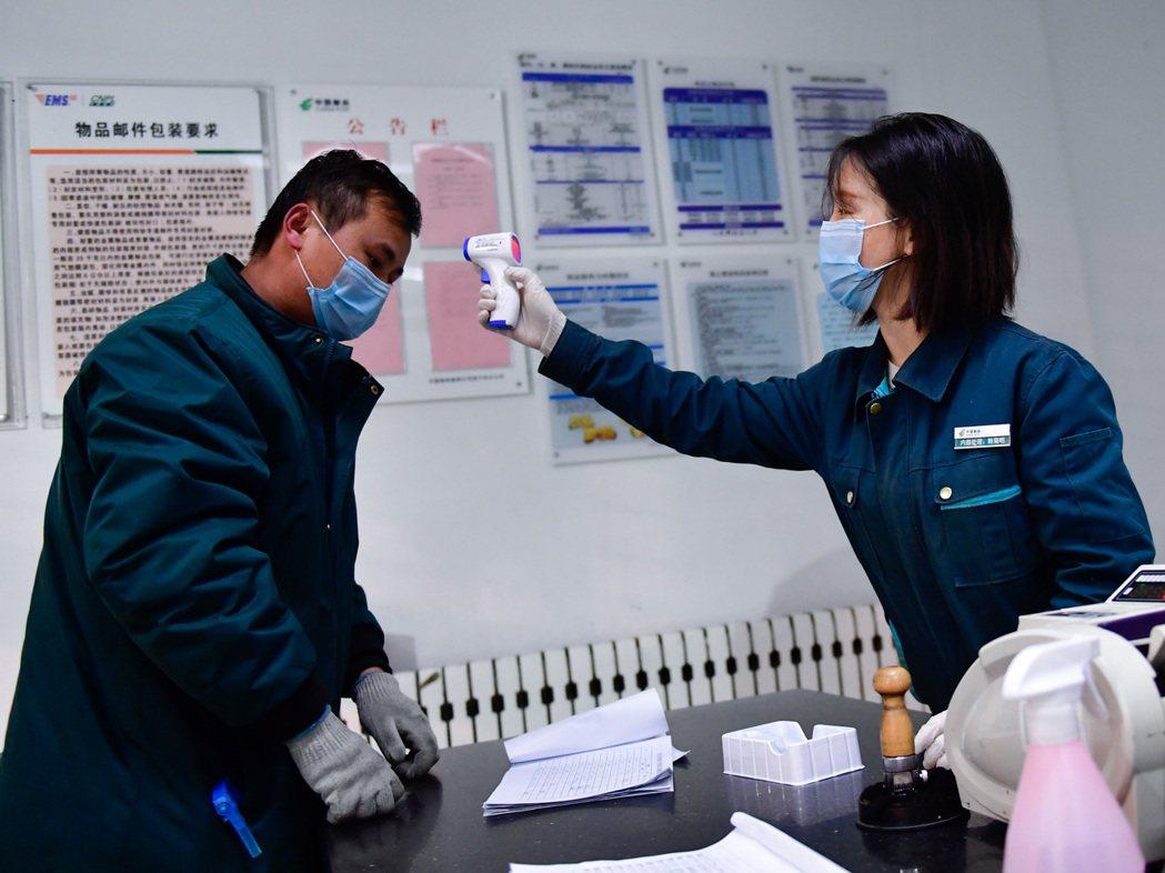 保障復工後的疫情防控,大陸各地使用測溫儀或額溫槍測量體溫。圖為青海西寧的郵政人員...
