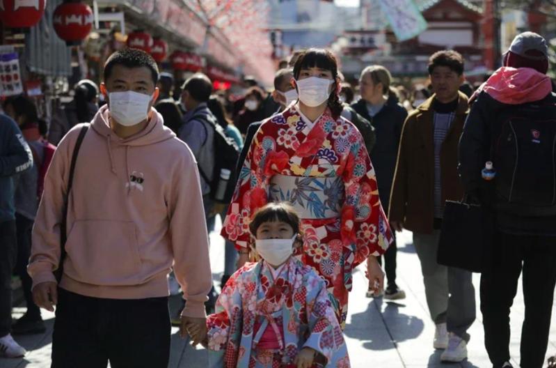 新冠肺炎疫情升溫,在日本街頭不少民眾戴上口罩。圖/美聯社