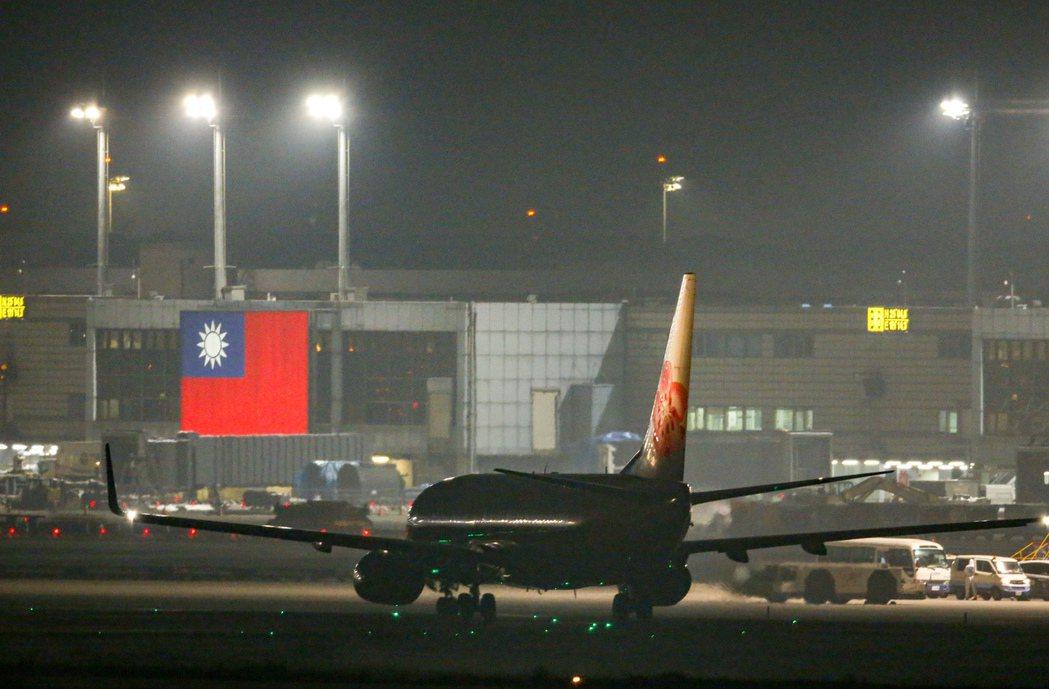 搭載鑽石公主上我國旅客的華航包機昨晚抵達桃園機場,飛機緩緩的駛過桃園機場的國旗前...
