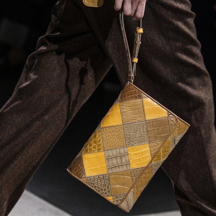 運用切割、拼接、異材質創作的繫繩手拿包,呼應大衣的拼接設計。圖/TOD'S提供