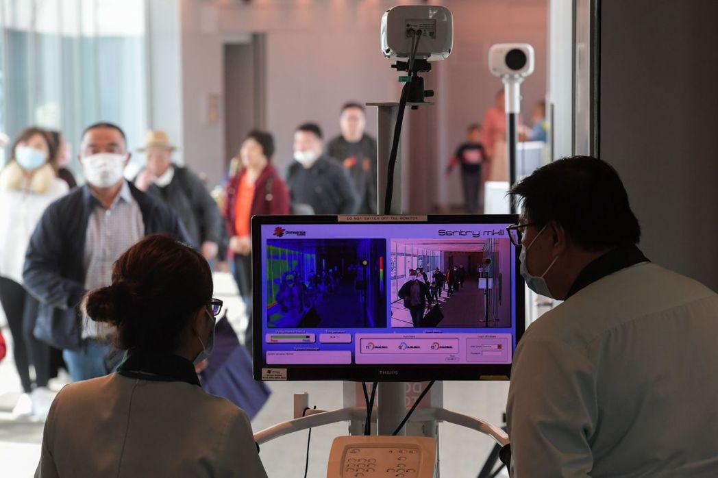 新加坡樟宜機場工作人員正使用熱掃描儀一一檢測來自大陸旅客的體溫。(法新社)