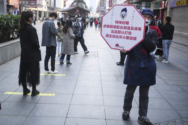 長沙一家網紅奶茶店畫出顧客排隊間隔,提醒民眾防疫「保持距離」。(中新社)