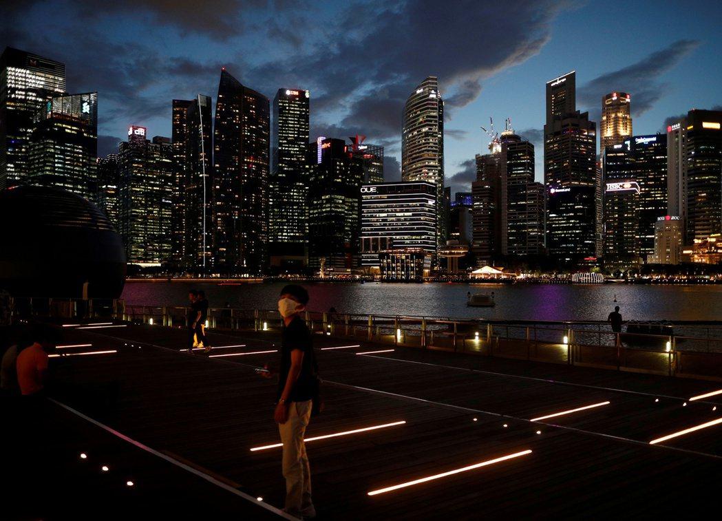 新加坡一名戴著口罩的男子19日在濱海灣岸邊走廊散步。 (路透)