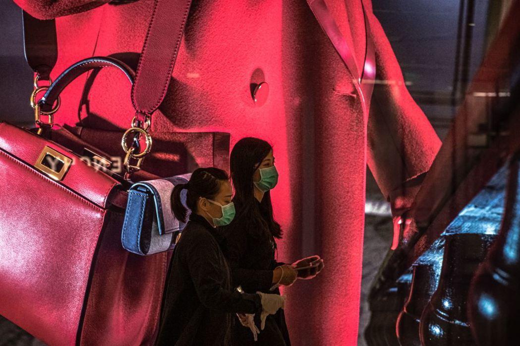 2月21日,北京一處購物中心裡,民眾戴上口罩逛街。 圖/歐新社