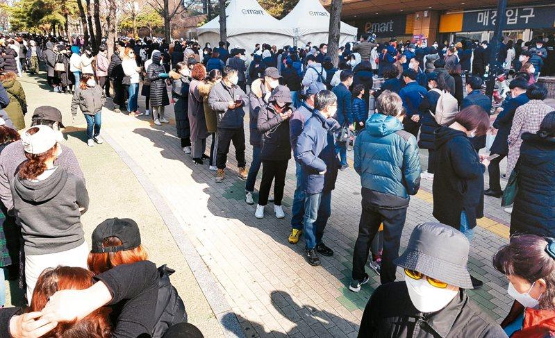 南韓大邱市民眾24日為買口罩大排長龍,所幸口罩供貨無慮。 路透