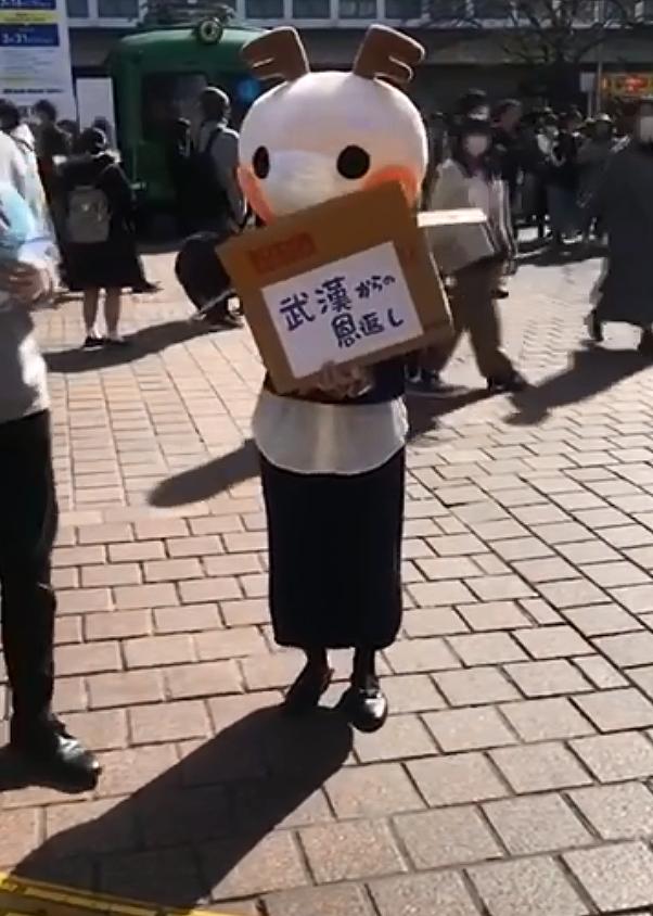 一位大陸女孩穿著可愛的玩偶裝在日本東京街頭發口罩。圖截自微博。