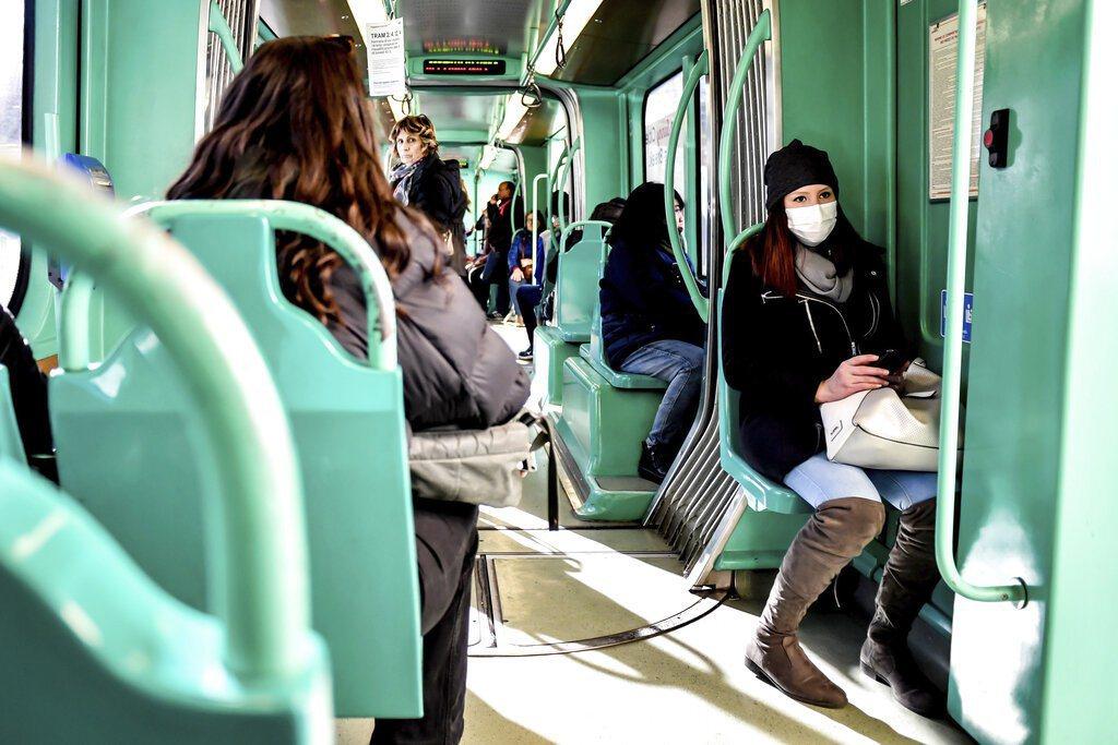 義大利米蘭電車上,人們戴著口罩防疫。 圖/美聯社