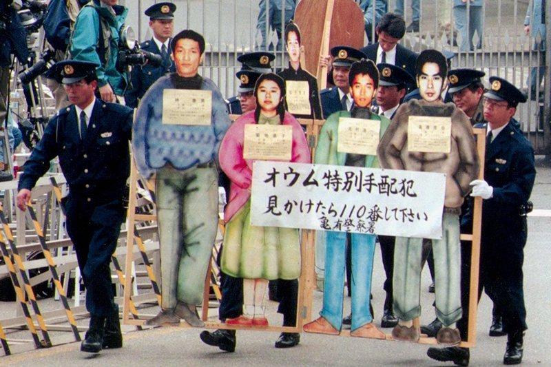 警察持奧姆真理教通緝犯的等身看板,攝於1996年。 圖/路透社