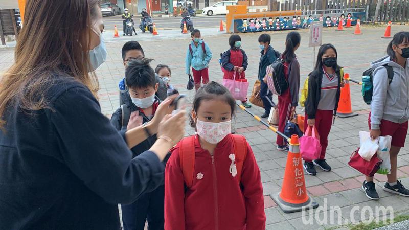 開學日,校園嚴陣以待,台南市新化國小為學生量體溫、蓋章及噴酒精,也請家長避免進入校園。記者吳淑玲/攝影