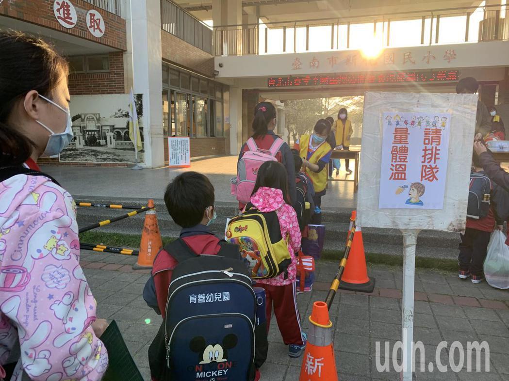 開學日,校園嚴陣以待,台南市新化國小為學生量體溫、蓋章及噴酒精,也請家長避免進入...