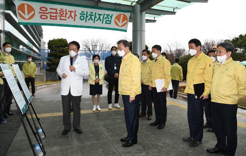 南韓總統文在寅(中)25日前往大邱視察,並聽取疫情簡報。圖/歐新社