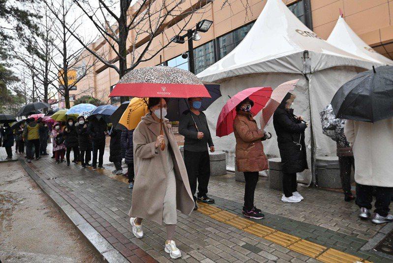 由於疫情持續升溫,南韓開始出現民眾瘋搶口罩情形。圖為25日大邱市一條排隊購買口罩人龍。法新社