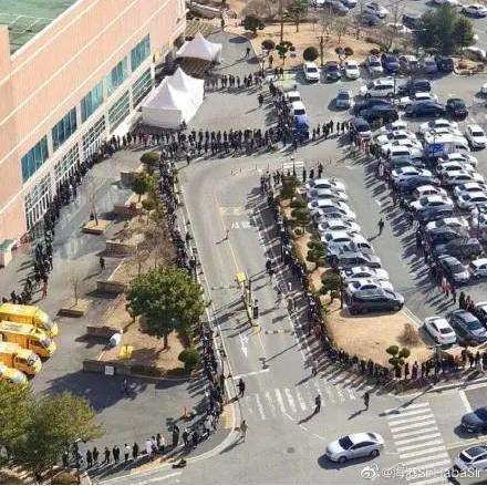 南韓爆發社區感染,已有近千名確診病例;圖為大邱市民排了數百公尺長隊買口罩。 (新...