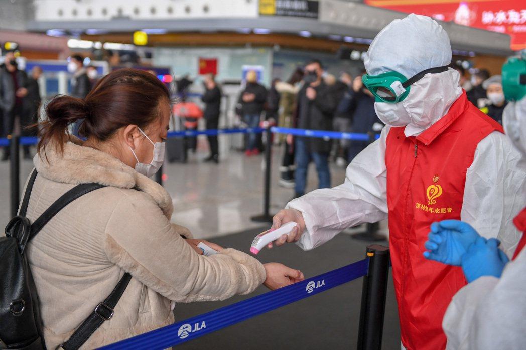 吉林長春龍嘉國際機場工作人員為進出機場人員測溫。 (新華社)