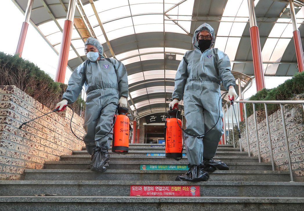 韓國濟州的工作人員,25日在一所研究院忙著消毒。  (新華社)