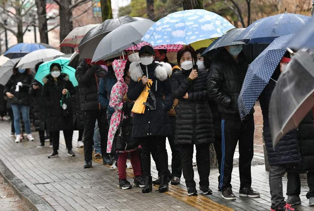 南韓大邱民眾廿五日在賣場外,冒雨排隊買口罩。 (法新社)
