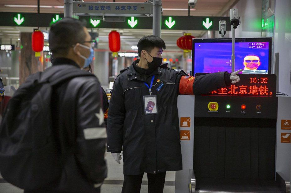 北京市新增10例新冠肺炎確診病例。圖為北京地鐵站內人員引導乘客通過熱影像儀來測量體溫。 (美聯社)