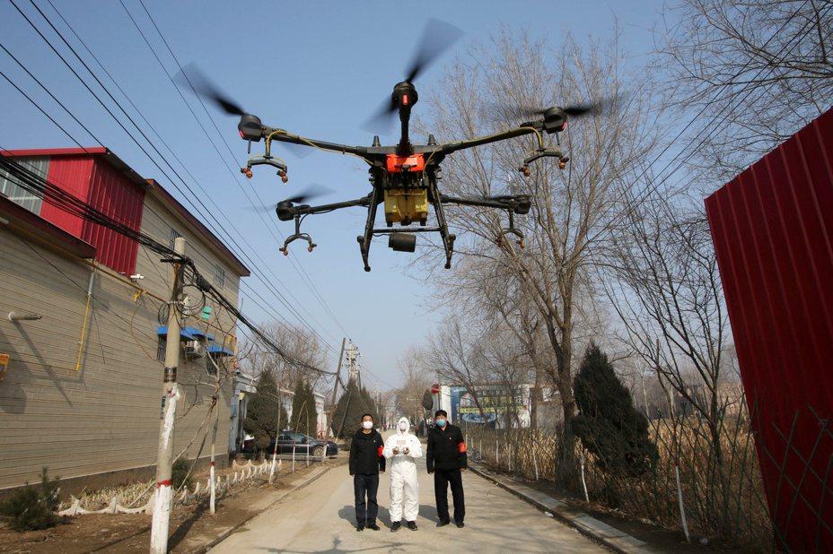 中國河北邯鄲市一處村莊內的志工,正利用無人機來噴灑消毒劑。 (路透)