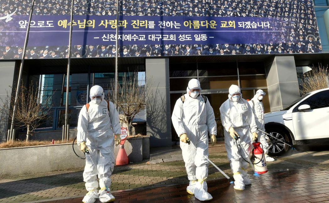 穿著防護裝備的工作人員19日在南韓大邱新天地教會前進行消毒。(法新社)