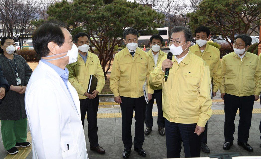 南韓總統文在寅(右持麥克風者)25日到大邱視察,與大邱醫學中心負責人談論疫情。(...