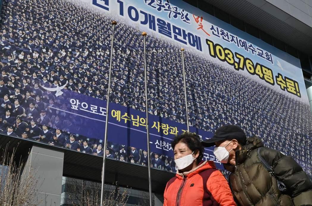 南韓多數新冠肺炎確診病例跟大邱新天地教會有關。圖為兩名路人走過該教會大樓前。(法...