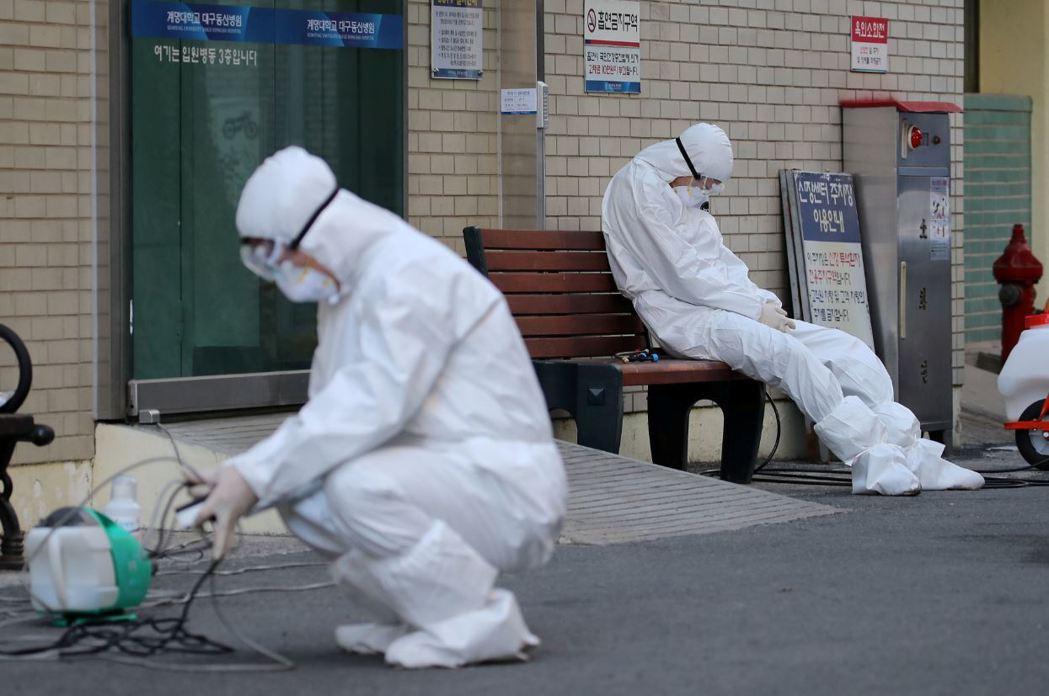 2月23日,南韓大邱一名穿戴防護裝的防疫人員在路邊稍做休息。 圖/路透社