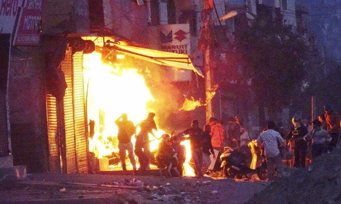 新德里亂鬥中,商店被縱火燒毀。 圖/美聯社