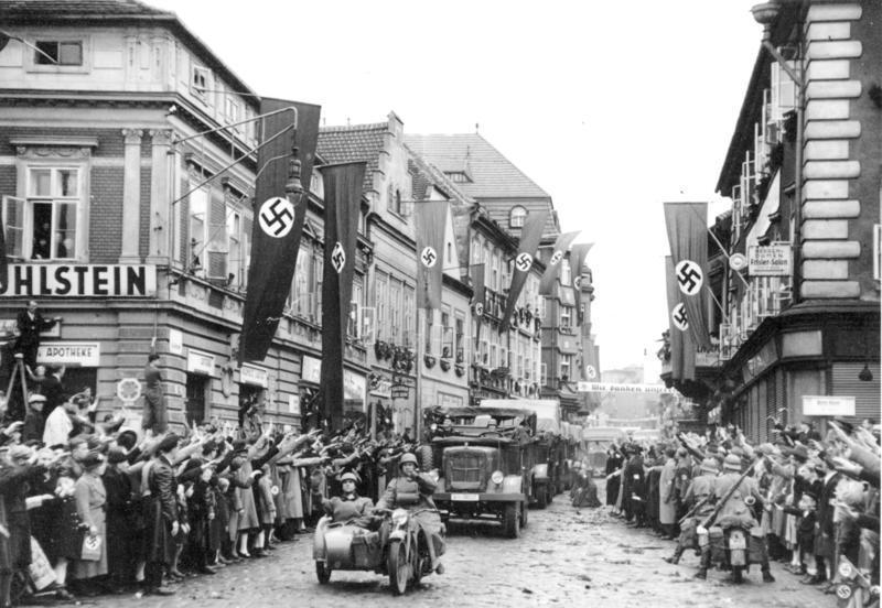 1938年,捷克斯洛伐克薩茨的德裔民眾對開入城區的德軍行納粹禮。 圖/摘自維基百...
