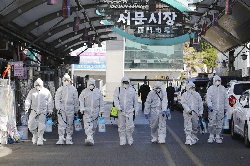 圖為南韓防疫人員針對大邱市的市場進行消毒。路透