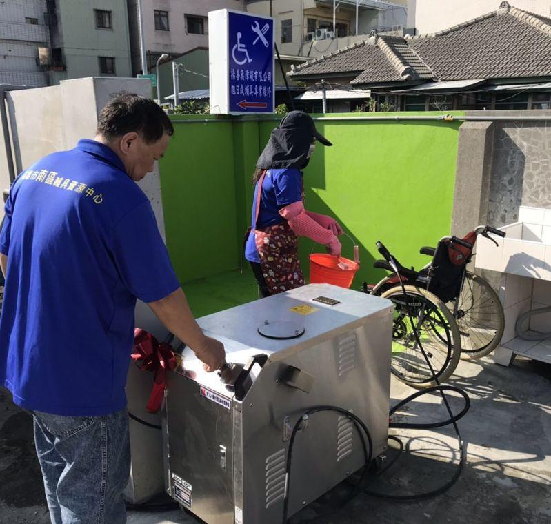 高雄市社會局二手輔具資源中心人員用日本進口的「臭氧高溫高壓水洗淨機」清潔二手輪椅。圖/高雄市社會局提供