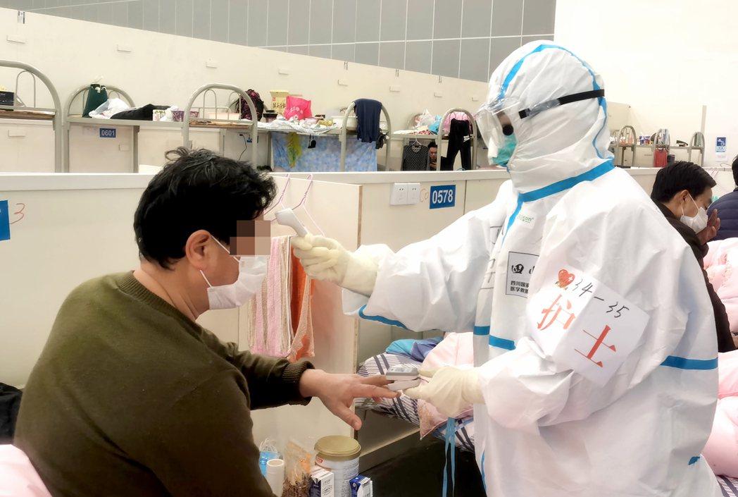 武漢漢陽方艙醫院內,醫護人員為患者測體溫。 (中新社)