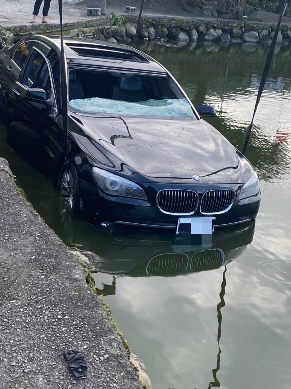 BMW 750轎車沒入釣魚池中,只能請拖吊車協助打撈。記者林昭彰/翻攝