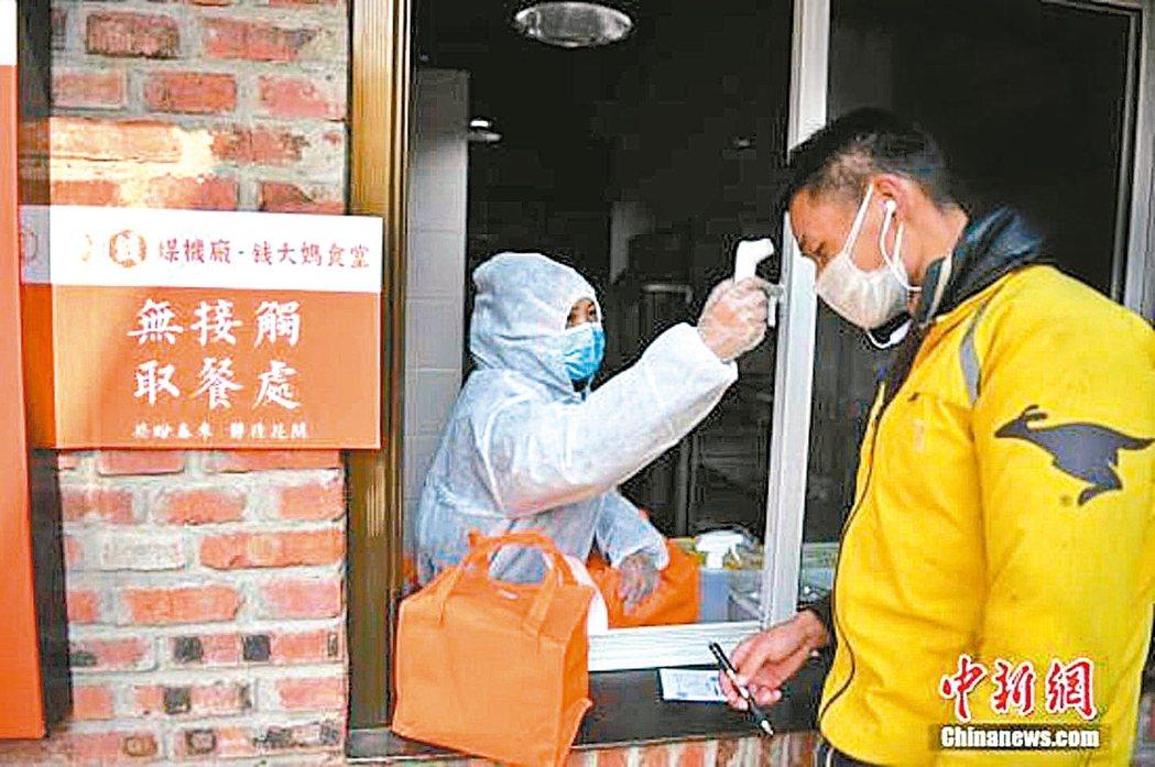 大陸商務部研究疫情結束後振興餐飲業措施。圖為餐廳員工對取餐外賣人員量體溫。 中新...