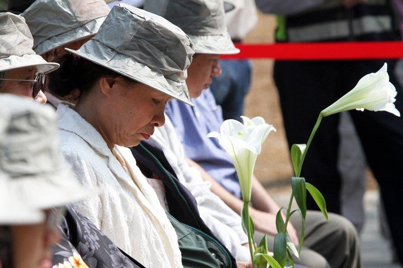 圖為2013年高雄市政府二二八和平紀念日活動,上百名受難家屬手持百合花默哀。 圖/聯合報系資料照