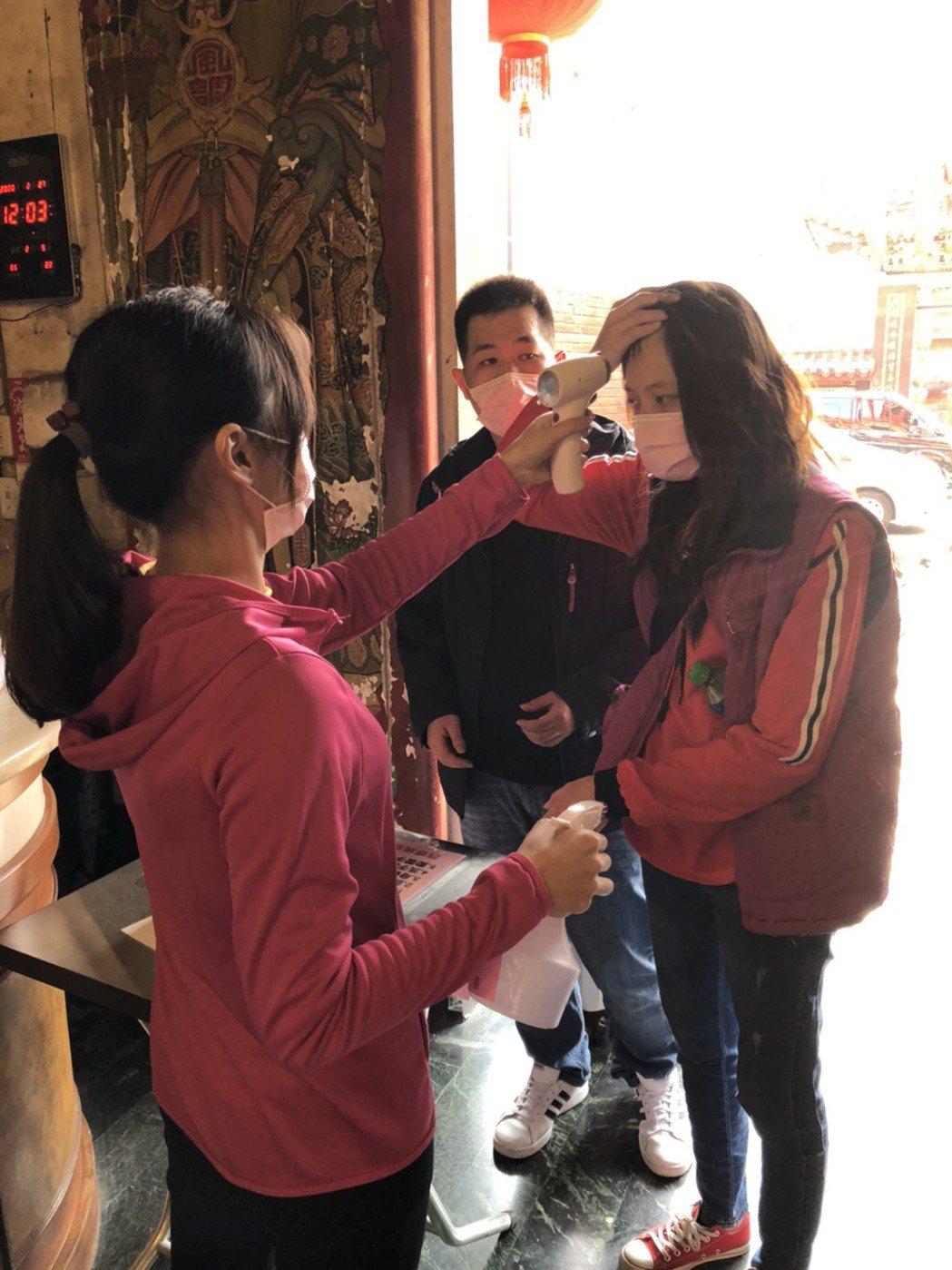 廟方派員在入口處幫民眾量體溫,勸導戴上口罩。圖/西螺福興宮提供