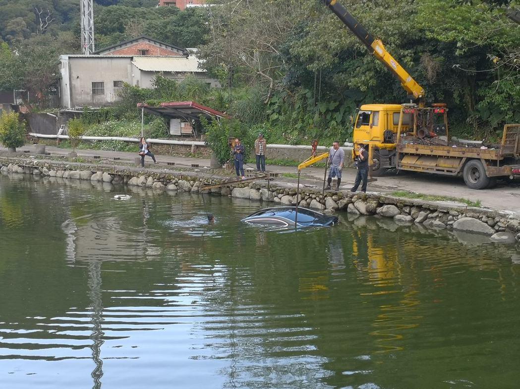 BMW 750轎車沒入釣魚池中,只能請拖吊車協助打撈。圖/翻攝細說淡水