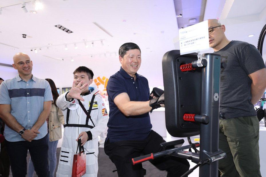 外貿協會秘書長葉明水(右二)在南港台灣精品館內,體驗獲獎精品-明躍國際「拳擊腳踏車」。貿協/提供