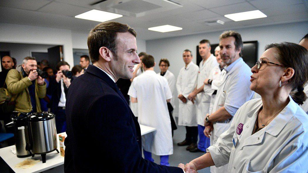 法國總統馬克宏27日到醫院為人員打氣。 歐新社