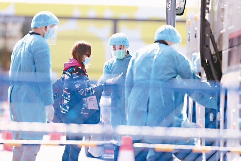陳時中表示是否要再調升對日本的旅遊警示,會以鑽石公主號旅客返回各國家後的健康狀況。圖為參與鑽石公主號郵輪防疫工作的日本醫護人員。 美聯社資料照