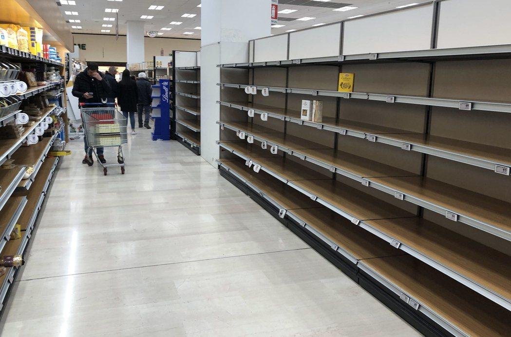 由於新冠肺炎疫情恐慌,民眾在超市大肆採購民生用品,架上的商品被掃購一空。(歐新社...