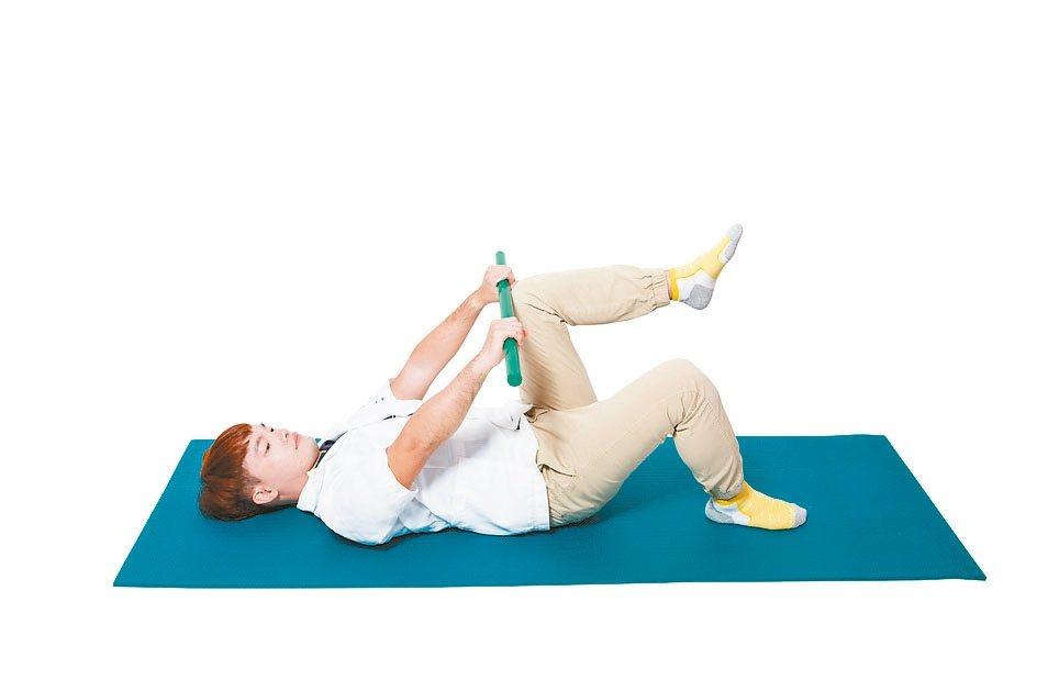 3.雙手往腳的方向移動,同時慢慢抬高左腳至膝蓋碰觸到棍子。 圖/摘自資料夾文化出...