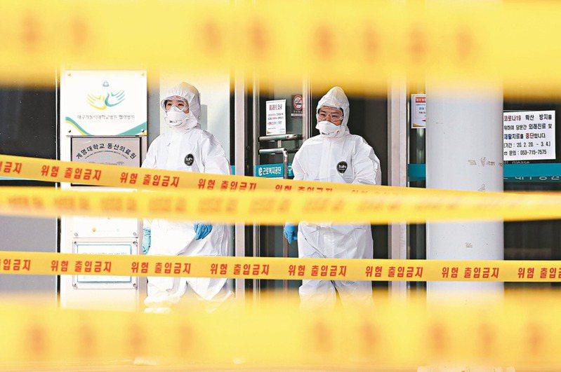 南韓大邱一家收治新冠肺炎患者醫院的醫護人員,一日穿防護裝進入黃色封鎖線內。 (法新社)