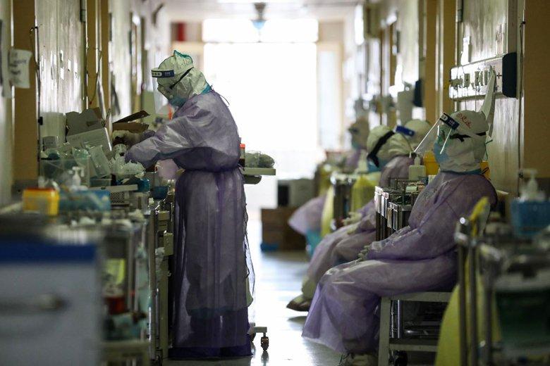 中國武漢一處醫院,醫療人員休息時也全身著防護裝防備。 圖/法新社