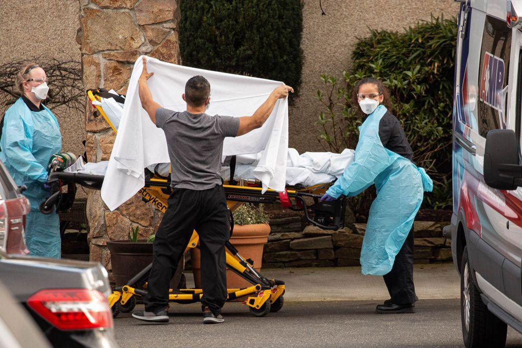 柯克蘭生命照護中心醫護人員2月29日將一名病人抬上救護車。(法新社)