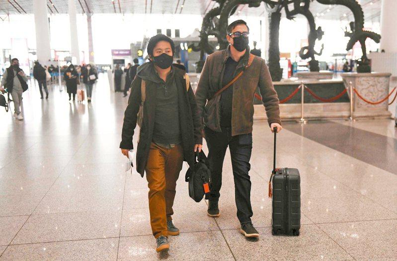 中國大陸上個月驅逐三名華爾街日報駐北京記者,圖為其中兩名記者在中國北京機場準備離境。 法新社