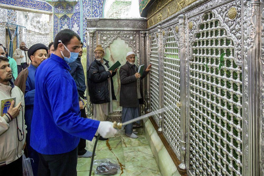 一名衛生工作人員2月24日對聖城科姆的聖墓大門進行消毒。(美聯社)