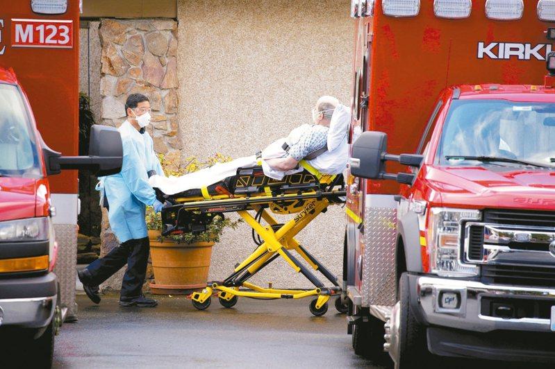 美國病例逐漸增加,圖為華盛頓州醫護人員將一名病患送上救護車。 路透